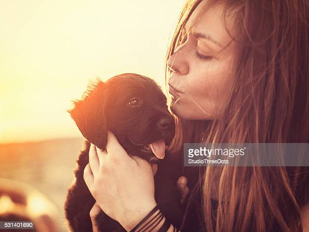 Happy woman with a puppy in her arms