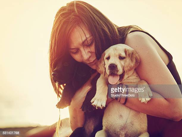 Happy woman with a two puppies in her arms