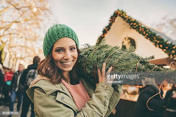 happy woman with a wrapped-up tree walking over the christmas market - carrying stock pictures, royalty-free photos & images