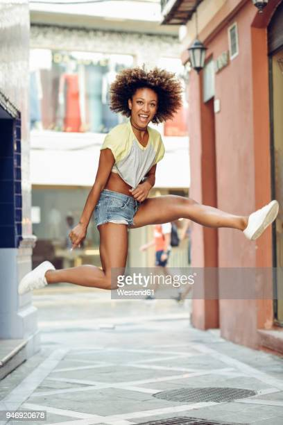 happy woman with afro hairstyle jumping in a lane - black alley stock photos and pictures
