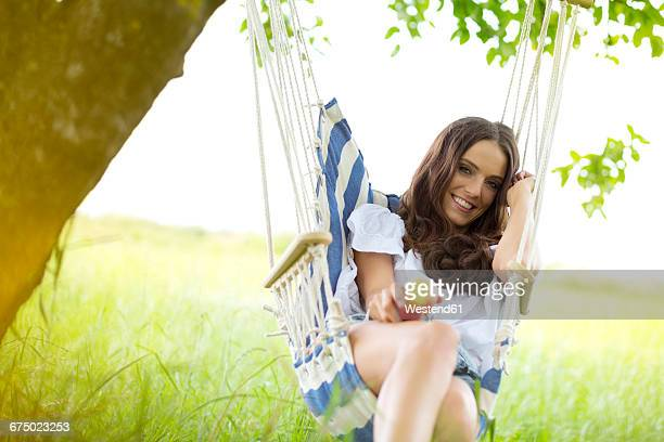 Happy woman with apple relaxing in a hanging chair under a tree