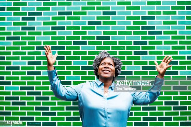 happy woman with arms in air - one mature woman only stock pictures, royalty-free photos & images