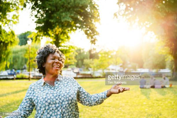 happy woman with arms out in park - wellbeing stock pictures, royalty-free photos & images