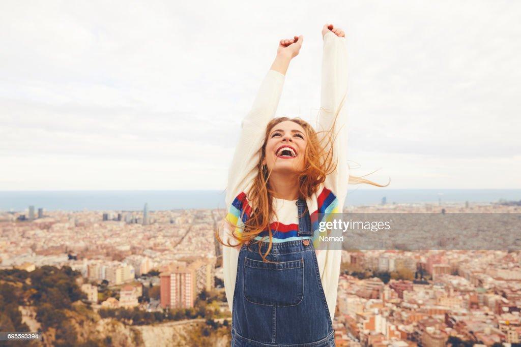 Mujer feliz con los brazos alzados contra el paisaje urbano : Foto de stock
