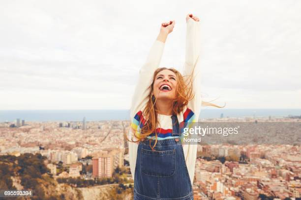 happy woman with arms raised against cityscape - emoção positiva imagens e fotografias de stock