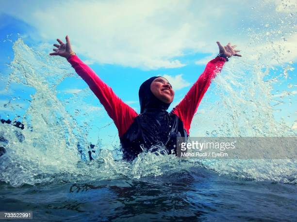 Happy Woman With Arms Raised Against Sky In Sea