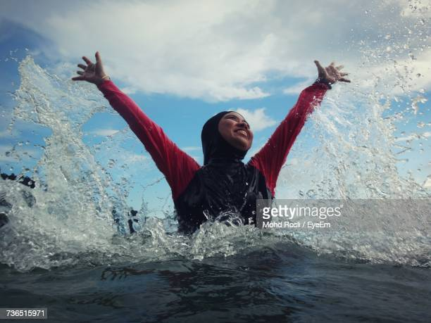 Happy Woman With Arms Raised In Sea Against Sky