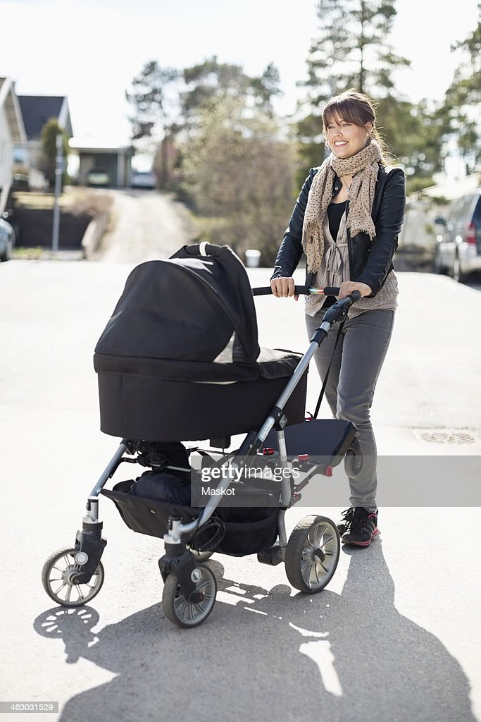 Happy woman with baby carriage standing on sunny street : Stock Photo