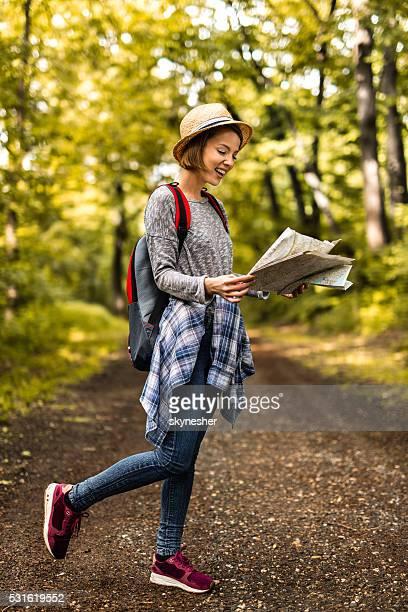 Femme heureuse avec sac à dos lire une carte dans la forêt.
