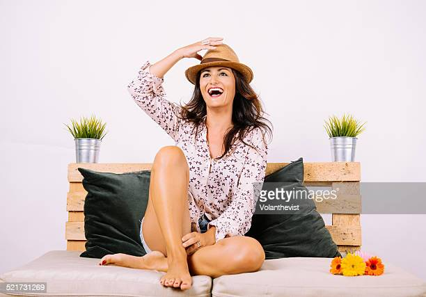 Happy woman with bare feet on the couch