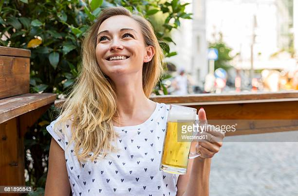 Happy woman with beer mug in a street restaurant looking up