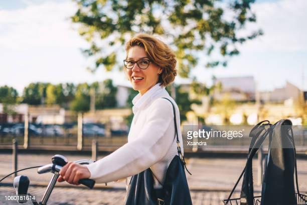 glückliche frau mit dem fahrrad in die innenstadt - 40 44 jahre stock-fotos und bilder