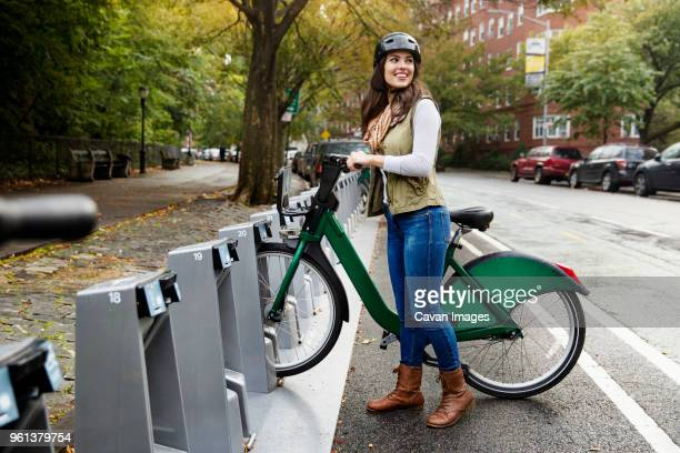 happy woman with bicycle looking away while standing at parking lot - bicycle parking station stock photos and pictures