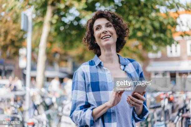 Happy woman with cell phone in the city