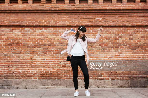 happy woman with cell phone listening to music on headphones at brick wall - bailar fotografías e imágenes de stock
