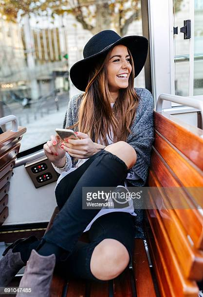 Happy woman with cell phone on a tour bus