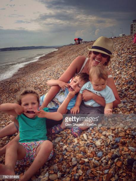 Happy Woman With Children Enjoying At Beach Against Cloudy Sky