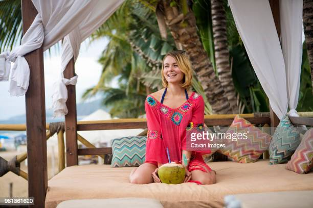 happy woman with coconut kneeling on four-poster bed at beach - mexican poster stock photos and pictures