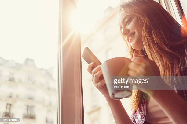 Happy woman with coffee cup texting on the open window