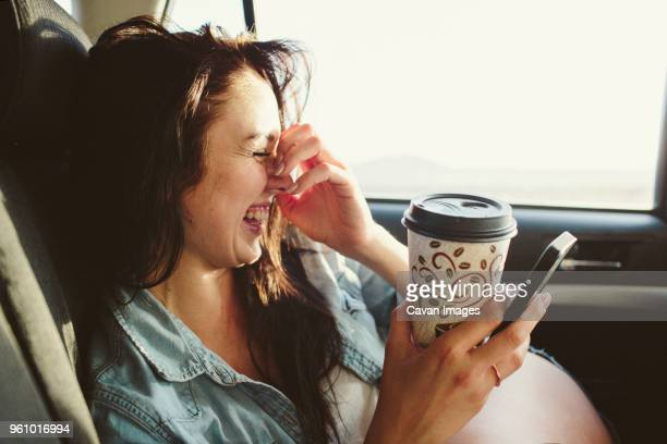 Happy woman with coffee cup using mobile phone while traveling in car