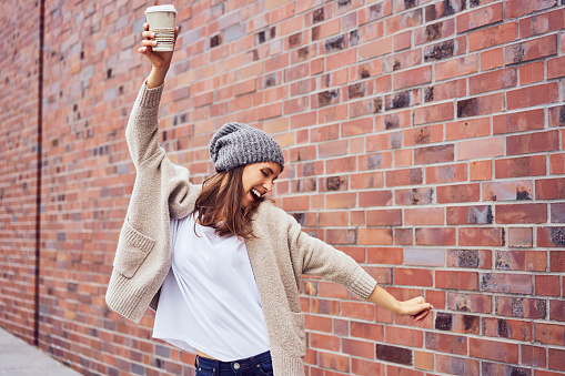 Happy woman with coffee to go singing and dancing on the street - gettyimageskorea