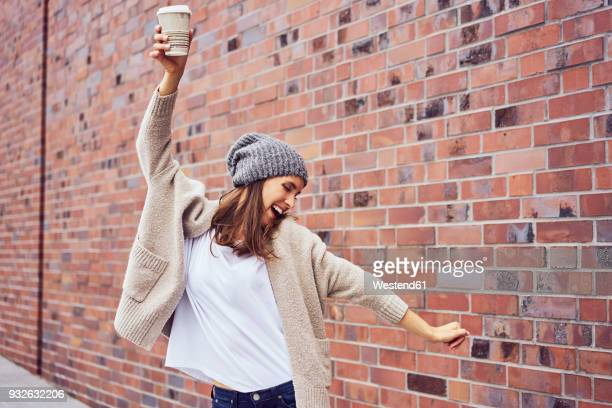 happy woman with coffee to go singing and dancing on the street - kaffee getränk stock-fotos und bilder