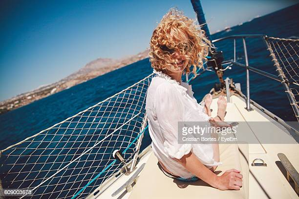 Happy Woman With Curly Hair Sitting On Boat Over Sea