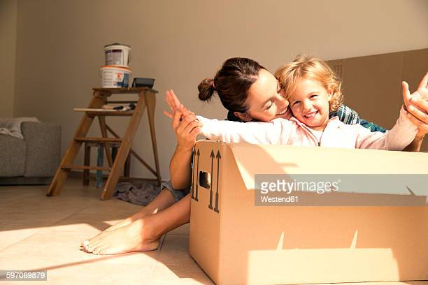 Happy woman with daughter sitting in cardboard box