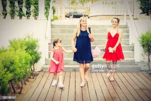 Happy Woman With Daughters Against Steps