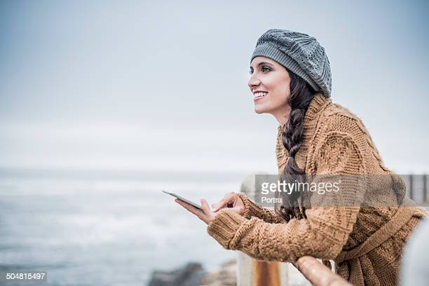 Happy woman with digital tablet at seaside railing
