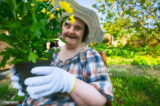 happy woman with down syndrome ready to planting flowers. gardening. - down syndrome stock pictures, royalty-free photos & images