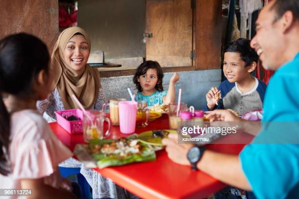 happy woman with family in restaurant - muslim boy stock photos and pictures