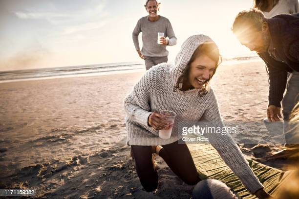 happy woman with friends and family on the beach at sunset - sorglos stock-fotos und bilder