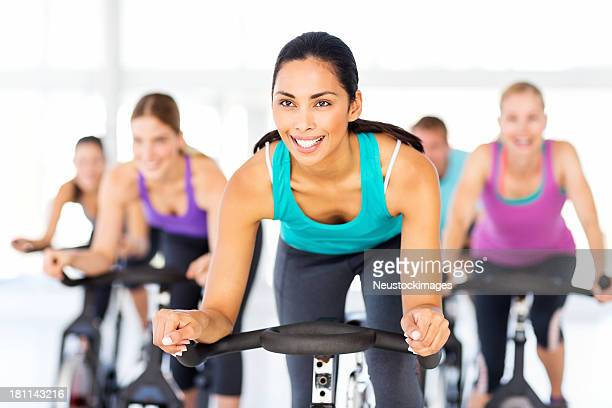Happy Woman With Friends Spinning In Health Club