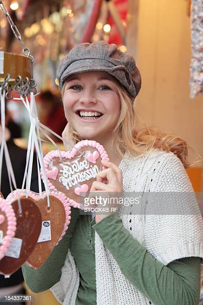Happy woman with gingerbread heart on a funfair
