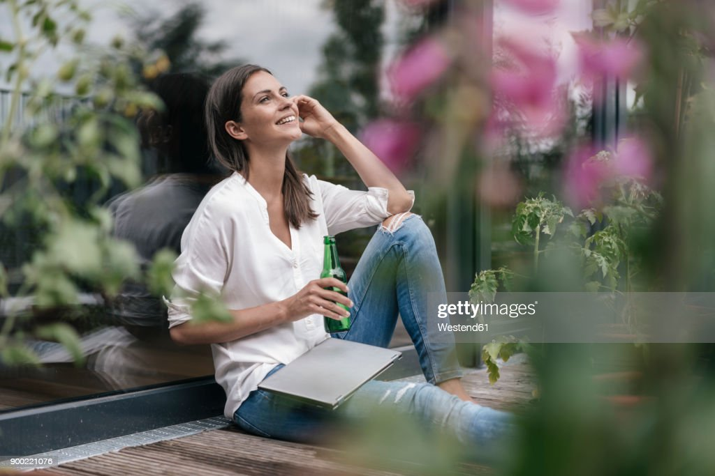 Happy woman with laptop and bottle sitting on balcony : Stock Photo