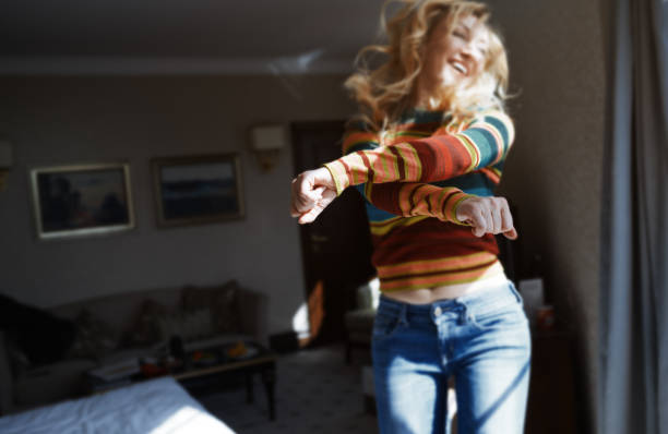 happy woman with long hair jumping and dancing at home - woman excited stock pictures, royalty-free photos & images