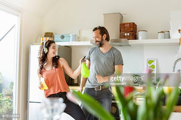 Happy woman with man in kitchen cleaning and listening to music