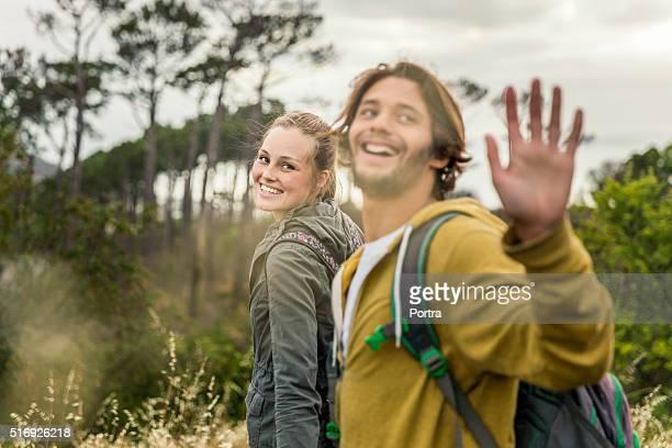 Glückliche Frau mit Mann winken während Wandern auf Feld