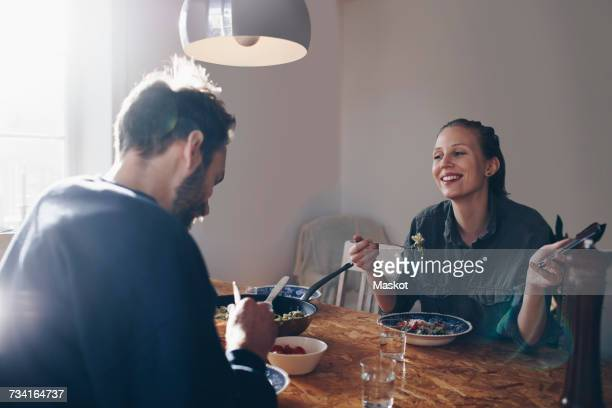 Happy woman with mobile phone looking at man while eating pasta at home