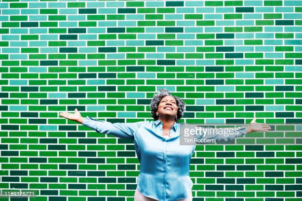 happy woman with outstretched arms - green colour stock pictures, royalty-free photos & images