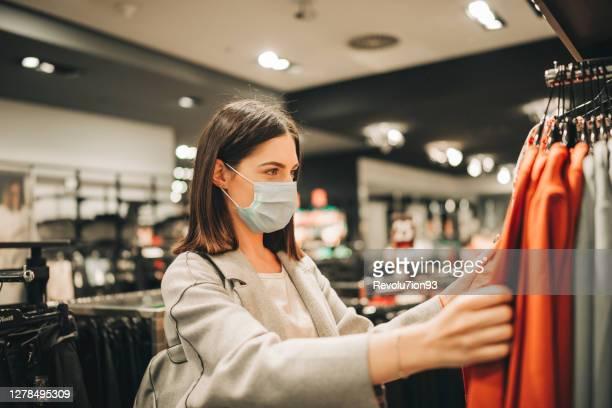 衣料品店で保護フェイスマスクを持つ幸せな女性 - オレンジ色のシャツ ストックフォトと画像
