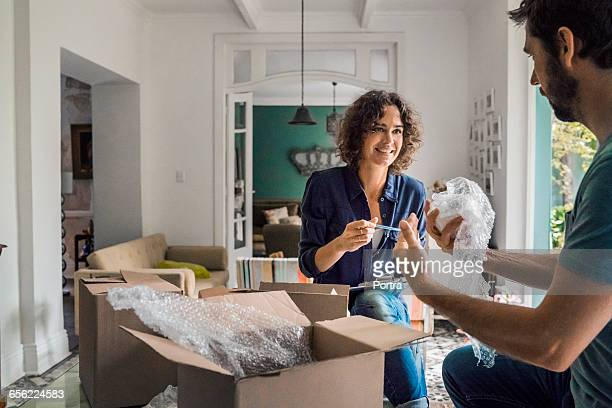 happy woman with spouse packing cardboard boxes - new home stock pictures, royalty-free photos & images
