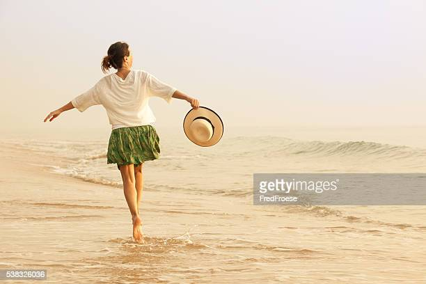 Happy woman with straw hut dancing on beach