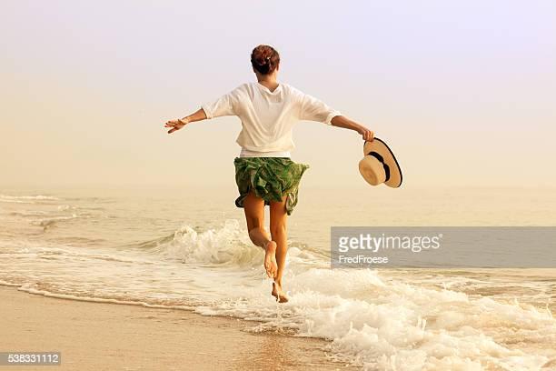 Femme heureuse sur la plage avec hutte de paille