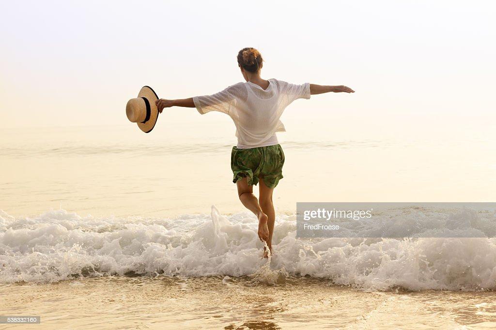 幸せな女性、ストローハットをビーチ : ストックフォト