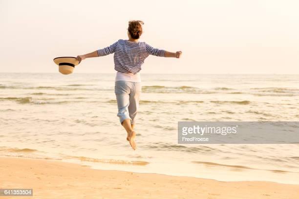 幸せな女性、ストローハットをビーチ