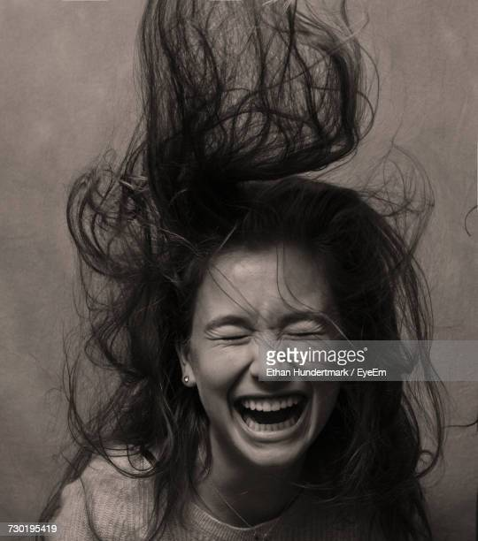 Happy Woman With Tousled Hair Against Wall