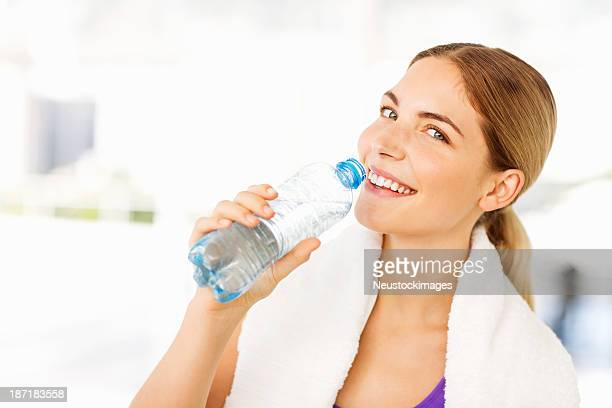 Happy Woman With Towel Around Neck Drinking Water