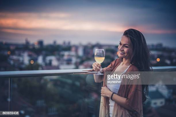Happy woman with white wine on a penthouse terrace.